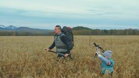 人们在麦田的美丽的山附近走 家庭旅行 由山的人环境 父母和孩子 股票录像
