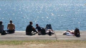 人们坐放松由湖边的甲板 库存照片