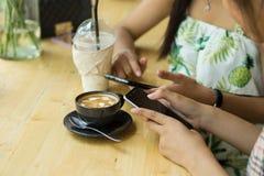 人们坐电话和饮用的咖啡在一张木桌上在餐馆 库存图片