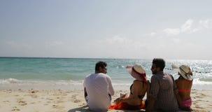 人们坐谈的海滩后面背面图、男人和妇女通信游人小组暑假 股票录像