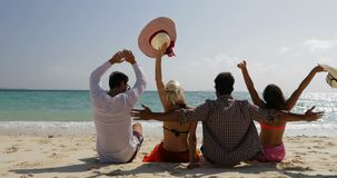 人们坐谈的海滩愉快的被举的手背面图、男人和妇女通信游人小组在夏天 股票视频