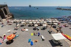 人们基于一个晴天在海滩在阿马尔菲海岸的在这个区域褶皱藻属,意大利阿马飞 免版税图库摄影