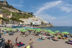 人们基于一个晴天在海滩在阿马尔菲海岸的在这个区域褶皱藻属,意大利阿马飞 免版税库存图片