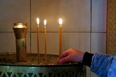 人们投入的小教会蜡烛关闭  免版税库存照片
