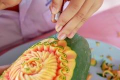 人们拿着在美丽的橙色或黄色花的果子刻刀,雕刻工艺 免版税图库摄影