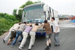 人们推进公共汽车。 免版税库存图片