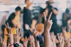 人们握两个手指在音乐会 免版税库存照片