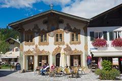 人们放松在与传统巴伐利亚人被绘的房子的小街道咖啡馆在背景在米滕瓦尔德,德国 库存照片