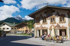 人们放松在与传统巴伐利亚人被绘的房子的小街道咖啡馆在背景在米滕瓦尔德,德国 免版税图库摄影