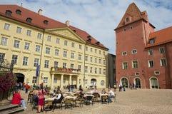 人们放松在街道咖啡馆在雷根斯堡,德国的历史部分的正方形 库存照片