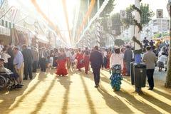 人们散步在日落和打扮在传统服装在塞维利亚` s 4月市场 图库摄影