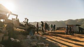 人们是在小山,当太阳落下与在左边的吉普汽车在Maejantai Akha村庄在小山时的 免版税库存图片