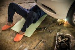 人们是汽车使用一把板钳的修理 免版税库存照片