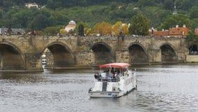人们沿漂浮在河伏尔塔瓦河的老布拉格桥梁和小船走 股票录像