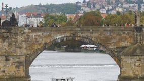 人们沿漂浮在河Vitava的老布拉格桥梁和小船走 股票视频