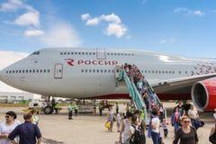 人们沿着走从一架大型飞机的梯子 免版税库存照片