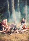 人们烤在火的香肠 人们享用野营的食物 免版税库存图片