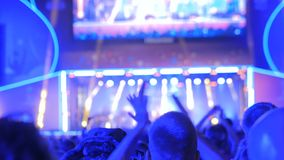 人们现出轮廓集会和拍手在夜在阶段前面的摇滚乐音乐会 股票录像