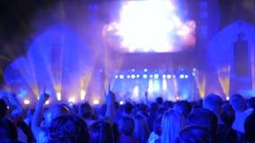 人们现出轮廓集会在夜在阶段前面的露天音乐会 股票录像