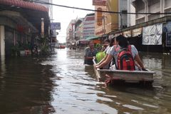 人们用在一条被充斥的街道的水应付在Rangsit,泰国,在2011年10月 免版税库存图片