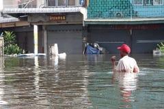 人们用在一条被充斥的街道的水应付在Rangsit,泰国,在2011年10月 库存图片