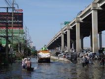 人们用在一条被充斥的街道的水应付在Rangsit,泰国,在2011年10月 图库摄影