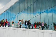 人们由全国奥斯陆歌剧院大厦的侧面墙走在奥斯陆,挪威 图库摄影