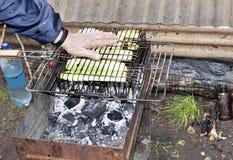 人们移交在格栅的热油炸物夏南瓜 免版税库存图片