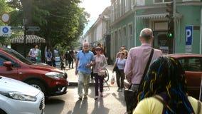 人们穿过路在汽车之间的红灯在Deribasovskaya和Ekaterininskaya街道的交叉点 股票视频