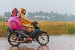 人们穿packable雨衣,当乘驾滑行车时 免版税库存照片