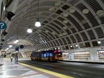 人们等待在先驱方形的驻地里面的合理的运输光路轨火车 免版税库存图片