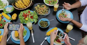 人们编组为在细胞聪明的电话油罐顶部角钢视图的健康素食食物,吃坐的朋友照相在 影视素材