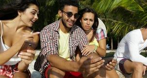 人们编组使用坐户外在棕榈树,愉快的微笑的人妇女朋友下的细胞聪明的电话通信 影视素材
