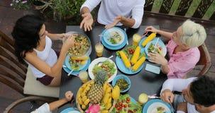 人们编组吃健康素食食物油罐顶部角钢视图,谈的朋友坐在表上的通信 股票录像