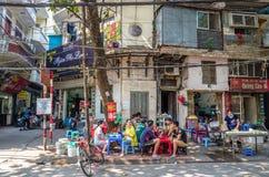 人们能看见食用他们的在街道旁边的食物早晨在河内,越南 免版税库存照片