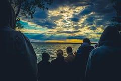 人们观看在一个悲剧的样式的太阳落山 免版税库存照片