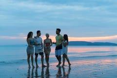 人们谈话在海滩在日落,走在晚上通信的海的年轻旅游小组 免版税库存照片
