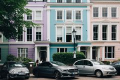 人们走通过报春花小山,伦敦,英国五颜六色的露台的房子  免版税库存图片