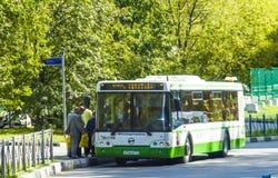 人们进入公共汽车在公共汽车站 库存图片