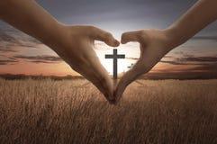 人们递做与里面明亮的十字架的心脏标志 免版税库存图片
