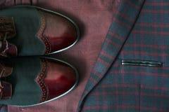 人伯根地衣服、蝶形领结和葡萄酒皮鞋在纺织品花呢背景 免版税库存照片