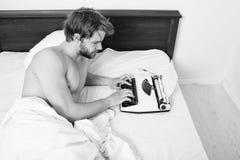 人作家在运转在新书的床白色床单放置 早晨启发概念 人创造新的章节用途 图库摄影