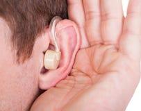 人佩带的助听器和细听安静的声音 库存图片