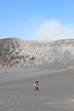 人佩带的帽子和在沙子海引导一辆自行车 库存照片