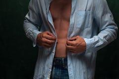 人佩带的牛仔裤和被解扣的衬衣特写镜头  库存图片