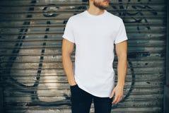 年轻人佩带的白色空白的T恤杉和蓝色 免版税库存图片