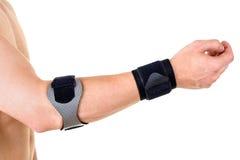 人佩带的腕子和手肘括号在演播室 库存照片