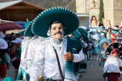 人佩带的面具和假装作为与深绿帽子的墨西哥流浪乐队在a期间 免版税库存图片