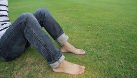 人佩带黑牛仔裤坐放松的绿草 免版税库存图片
