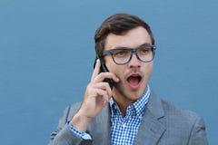 年轻人使人惊奇谈话在他的在蓝色背景的手机 库存照片